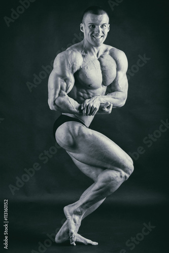 Fotografie, Obraz  A man with a gorgeous muscular body on a black background