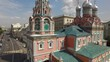 Orthodox church in Moscow city center. Narrow historic old street road day traffic. Aerial view.