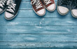 Three pairs of sneakers on a wooden blue background