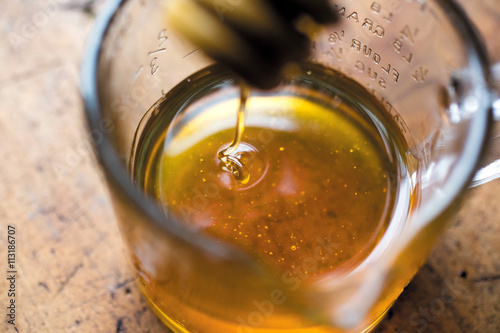 Honey dripping into glass jug