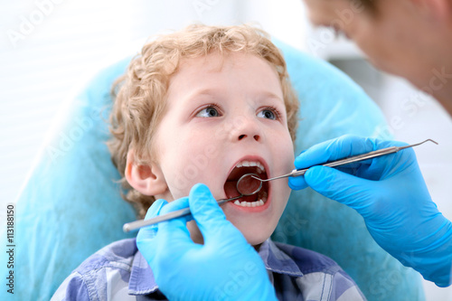 Close up of boy having his teeth examined by a dentist плакат