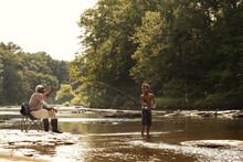 Grandfather And Grandson Fly Fishing In River