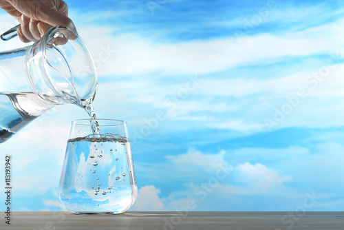 Fresh and clean drinking water being poured from jug into glass on sky background