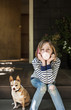 Young girl (10-11) sitting with dog outdoors