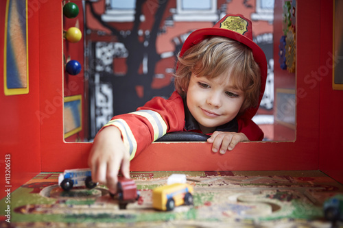 Boy dressed in firefighter costume and playing with toy