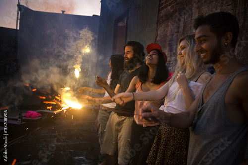 Happy friends enjoying with lit sparklers at garden party during sunset