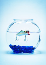Fishing Hook In Fishbowl Against Blue Background