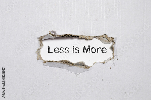 Fotografía  The word less is more appearing behind torn paper.