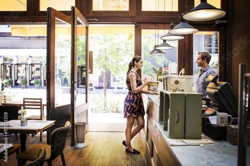 Woman talking to man at cafe counter