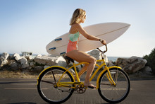 Teenage Girl With Surfboard Riding Bicycle On Road