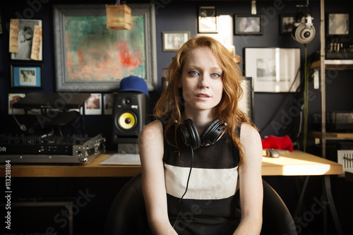 Portrait of female DJ sitting at sound recording studio Poster