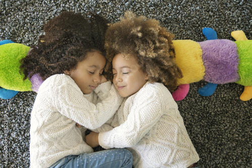 Two girls sleeping together on floor