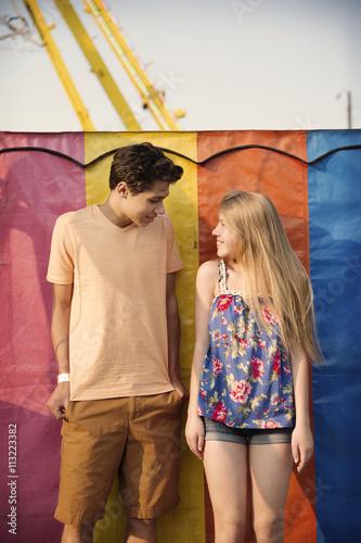 Papiers peints Attraction parc Happy couple standing against multi colored metallic wall at amusement park