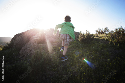 Boy (4-5) running up hill
