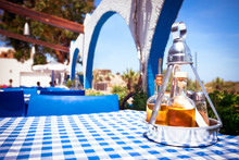 A Table With A Tablecloth At A Greek Restaurant