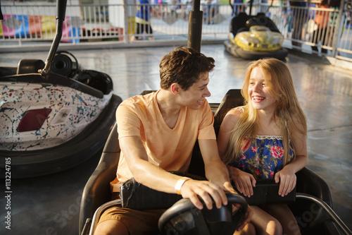 Papiers peints Attraction parc Happy couple riding bumper car at amusement park