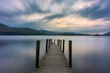 Wooden jetty leading out into lake with dramatic clouds in sky. Ashness, Derwentwater, Keswick, Lake District, UK.
