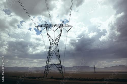 Electricity pylon in desert under cloudy sky