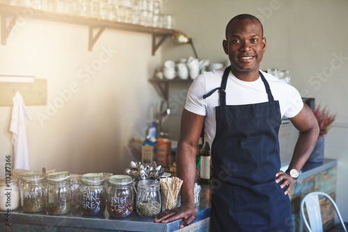 Fotografía  Handsome black entrepreneur stands by cafe counter