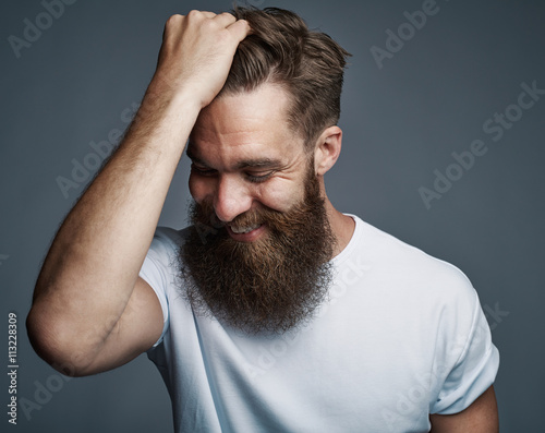 Fényképezés Laughing bearded man holding hair and laughing