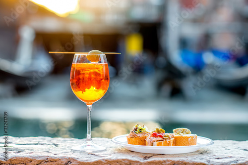 Spritz Aperol drink with venetian traditional snacks cicchetti on the water chanal background in Venice Canvas Print