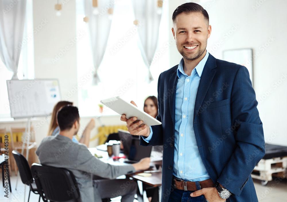 Fototapeta Businessman using his tablet in office