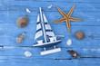 Maritime Dekoration mit Seesternen, Muscheln, Holzschiff, Badelatschen, Sand auf Holzhintegrund