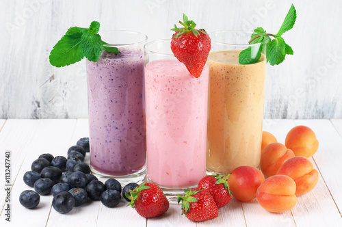 Recess Fitting Milkshake Three various protein milkshakes in glasses with fruits on rustic white wooden background.