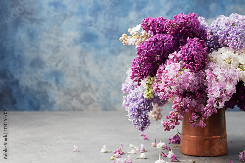 Foto op Plexiglas Lilac Bunch of lilac flowers in a cooper vintage jug. Blue background Copy space