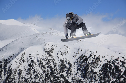 Snowboard rider jumping on mountains. Extreme freeride sport. Wallpaper Mural