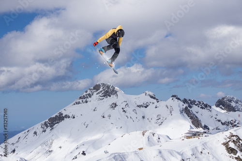 Snowboard rider jumping on mountains. Extreme freeride sport. Canvas Print