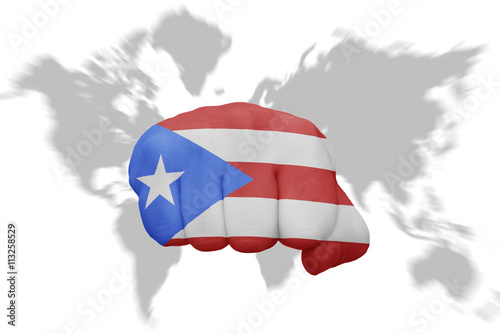 fist with the national flag of puerto rico on a world map ...