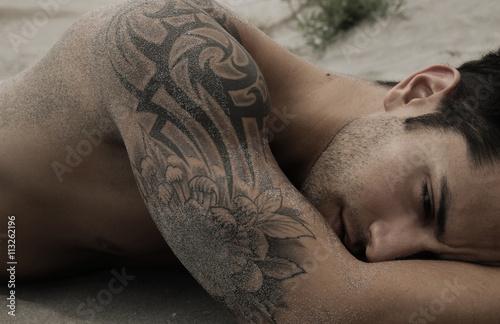 Fotografie, Obraz Handsome male lying on the sand