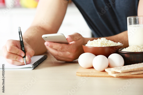 Foto Man counting calories on table