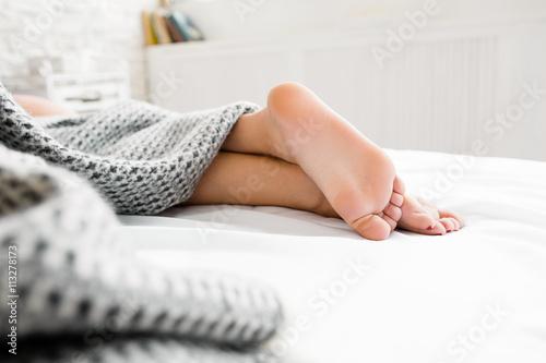 Plakat Sypialni kobieta cieki pod koc. Piękni cieki sypialna kobieta pod koc na jej łóżku. Sypialnia na tle. Skoncentruj się na pięknych stopach. Wolna przestrzeń