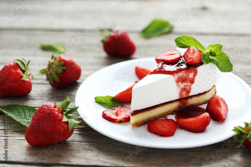 obraz dibond Strawberry cheesecake on plate on grey wooden table