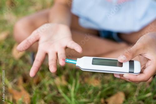 Fotografía  Girl testing diabetes on glucose meter
