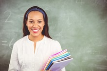 Portrait Of Smiling School Teacher Holding Books In Classroom