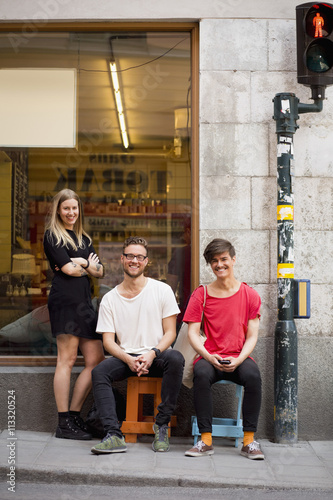 Full length portrait of happy young friends on sidewalk