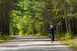 cyclist rides along the road in the forest