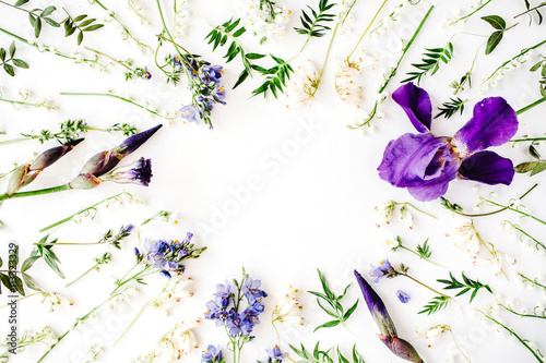 Poster Muguet de mai floral frame with purple iris flower, lily of the valley, branches, leaves and petals isolated on white background. flat lay, overhead view