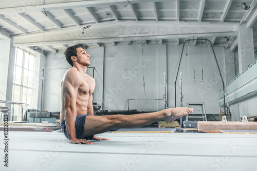 caucasian man gymnastic acrobatics equilibrium posture at gym background Fototapeta
