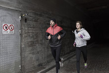 Sporty Couple Running In Tunnel