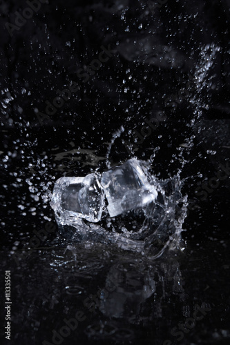 Photo  Two ice cube flying with splashes on a black background