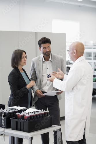 Engineer explaining machine part to business people in industry