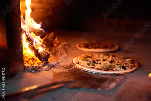 Poster Pizzeria raw pizza lay down stove with the fire on blade.