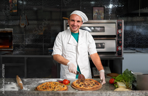Chef cuts freshly prepared pizza on a wooden substrate.