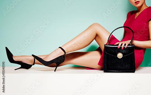 Fototapeta Beautiful legs woman with black high heels shoes and handbag purse