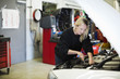 Mid adult female mechanic repairing car engine at auto repair shop