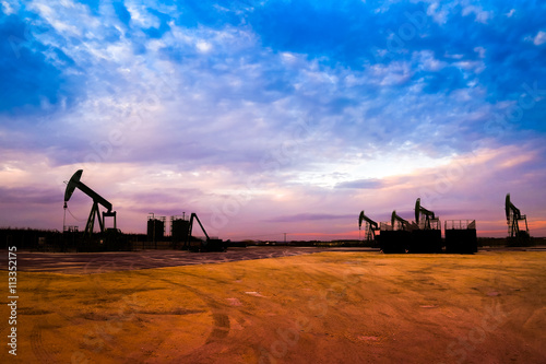 Fotografia  Silhouette of Oil pumps at oil field with sunset sky background
